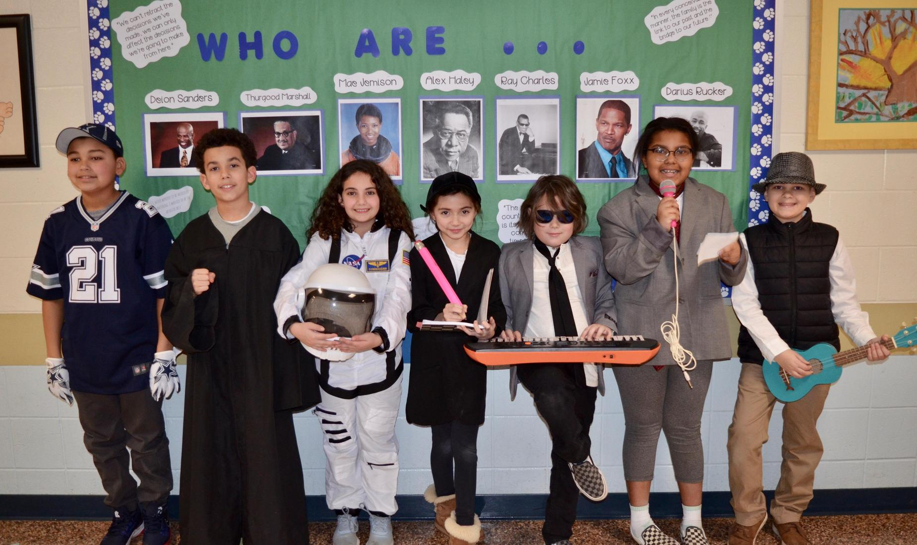 7 elementary students dressed as famous African American, baseball player, astronaut, musician