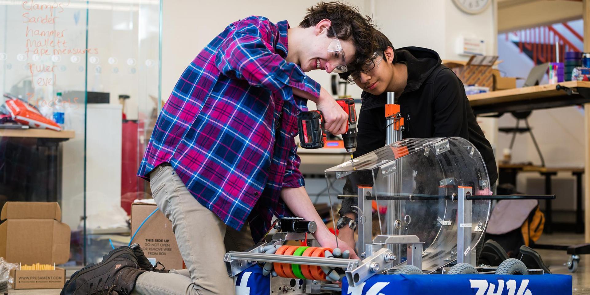 """两名学生在""""北方地平线""""7416团队的2019-2020机器人上工作."""