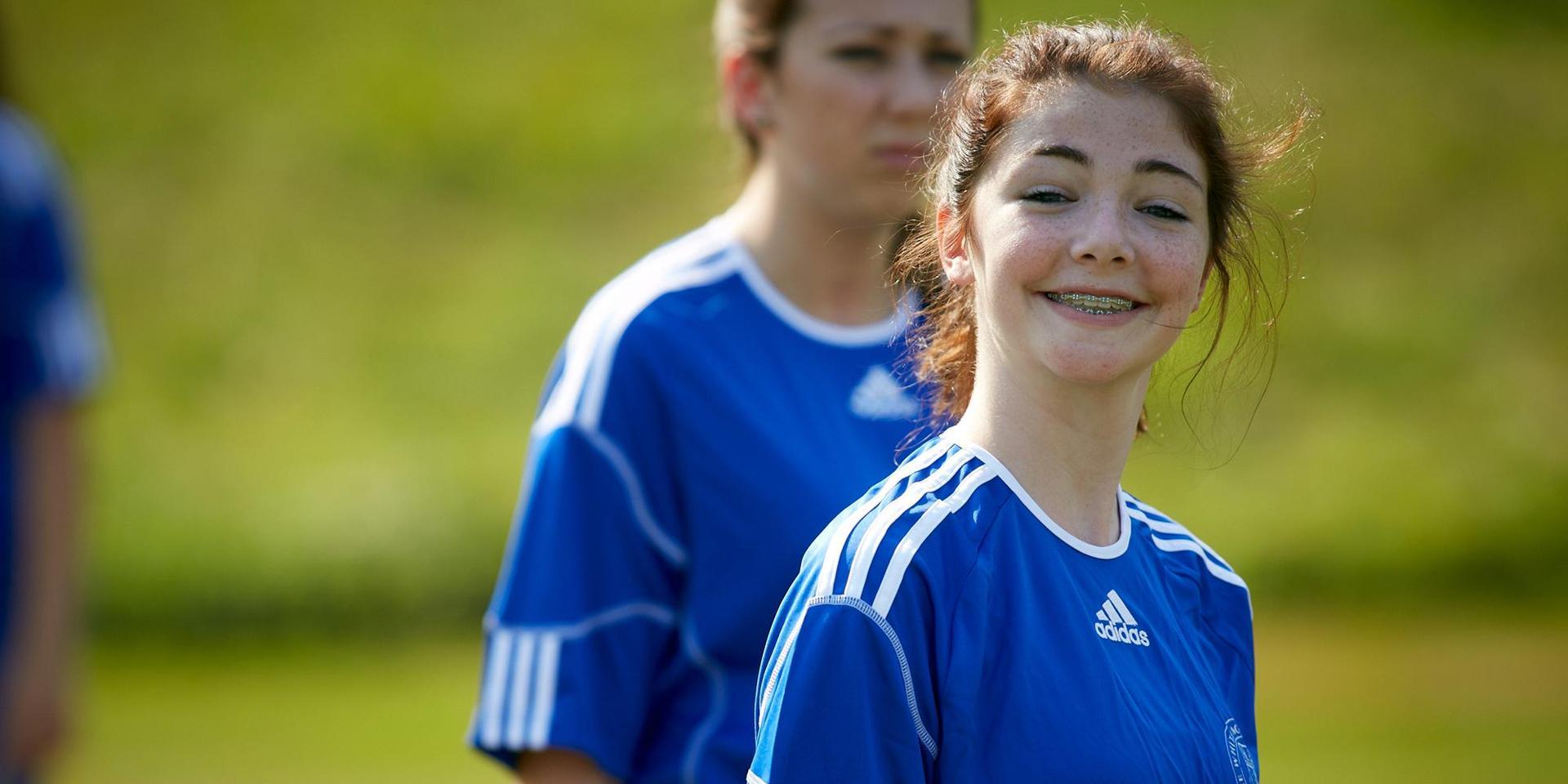 一个学生足球运动员对着镜头微笑.