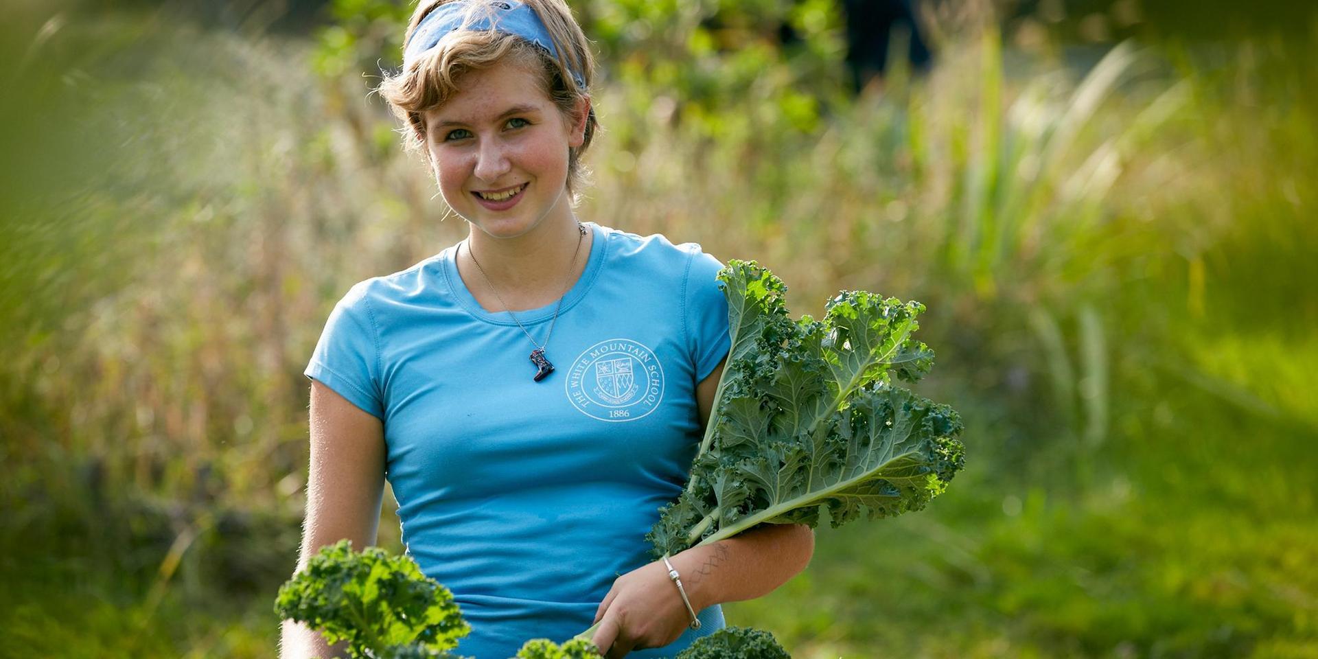 一个学生拿着刚收获的绿叶蔬菜.