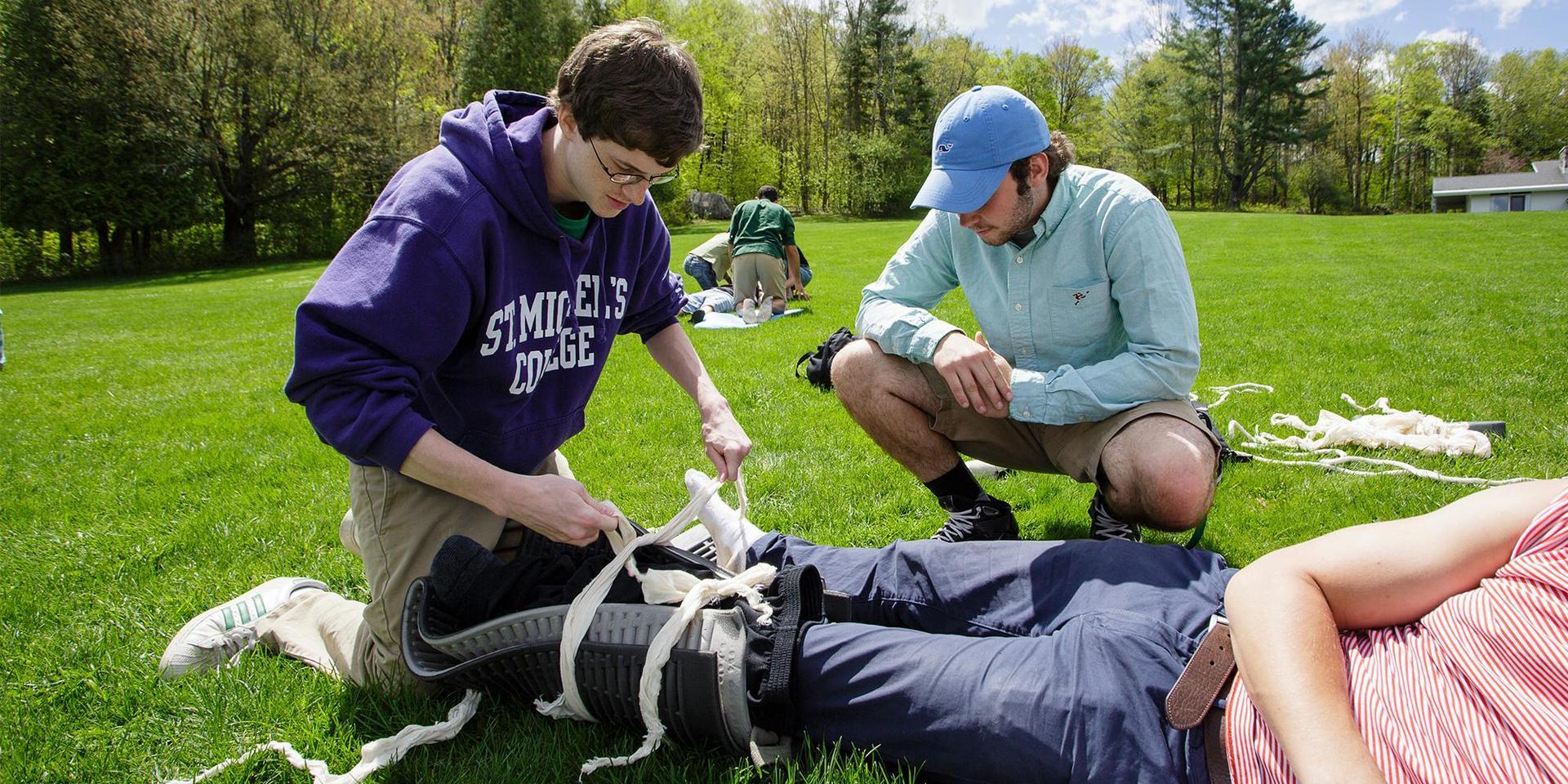 一个学生正在野外急救课上给另一个学生做夹板.