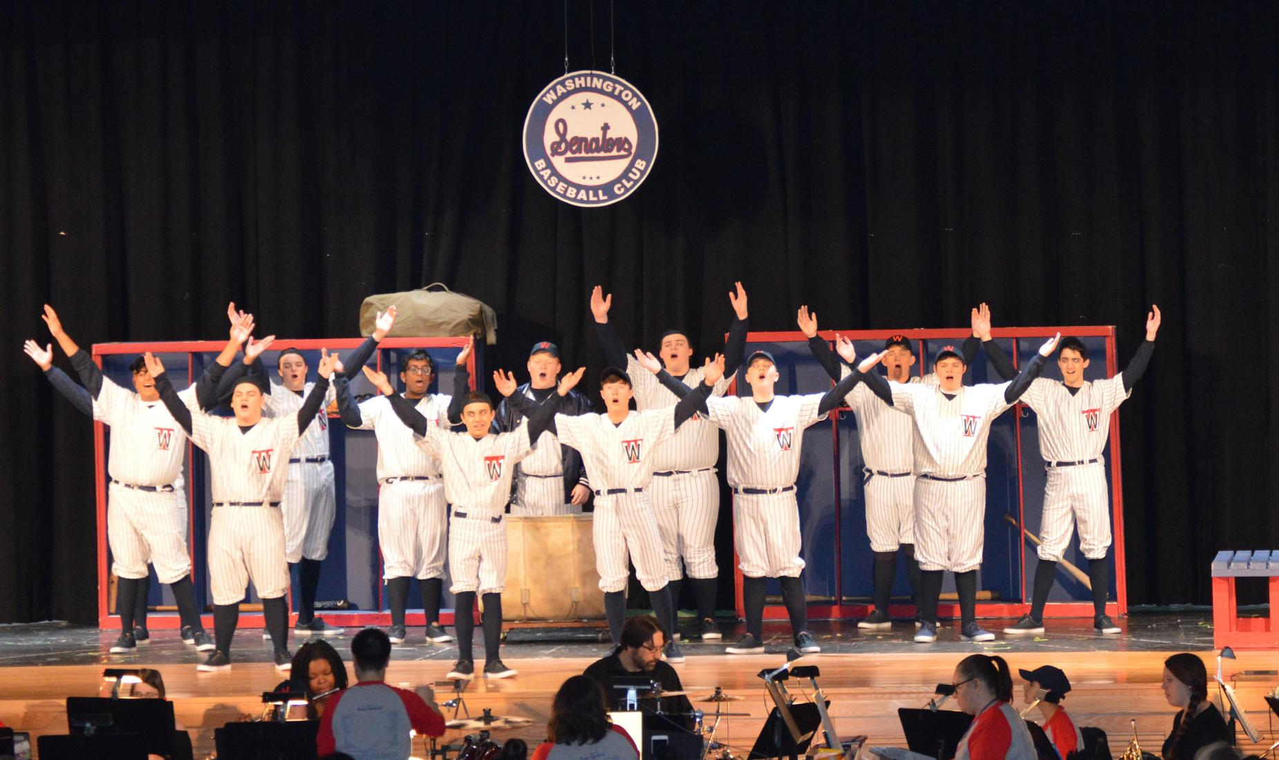 11 students wearing white with navy striped Washington Senators uniforms. They are singing with their arms up in the air.