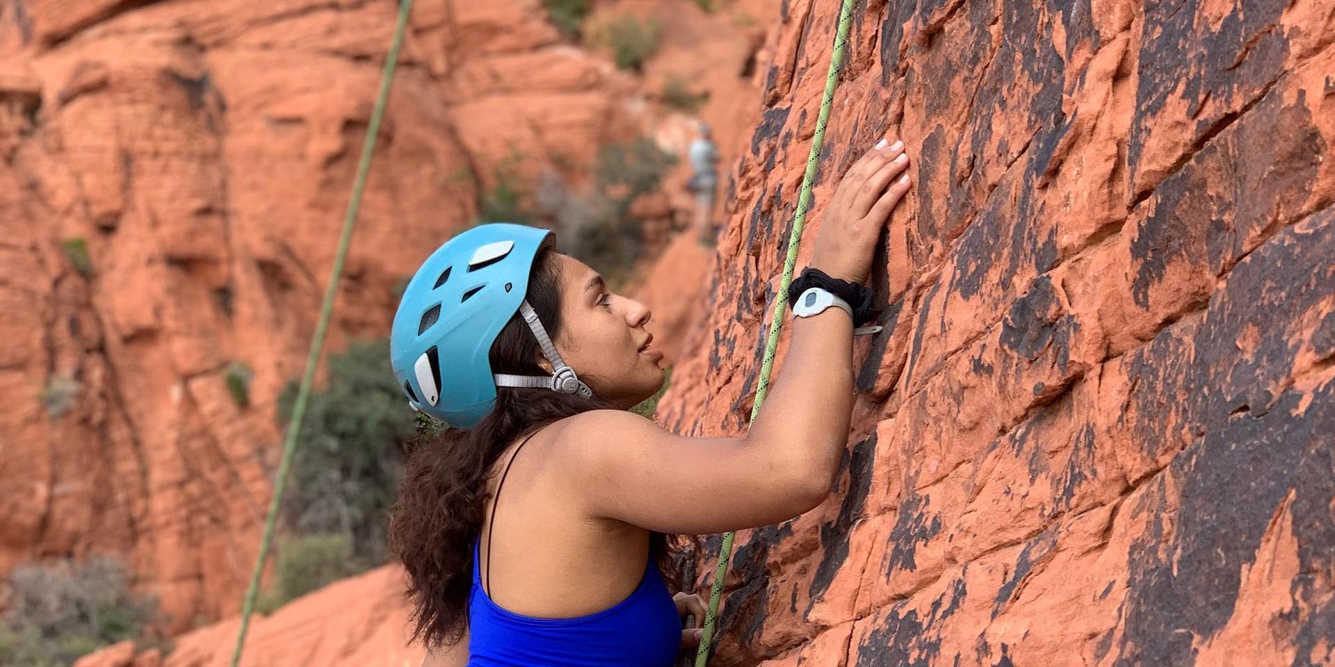一名学生正在攀登一处红色悬崖.