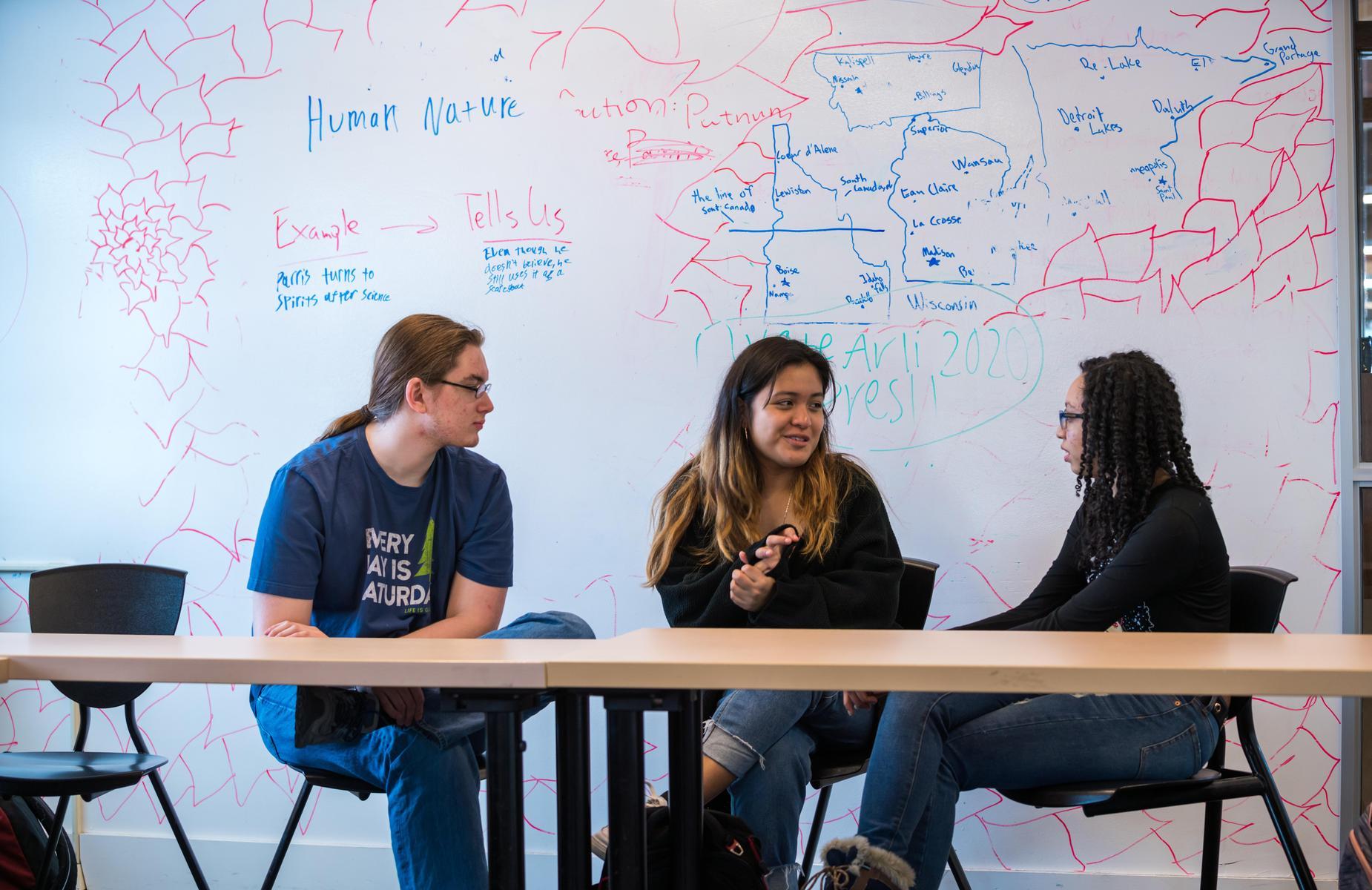 三个学生在教室里讨论.