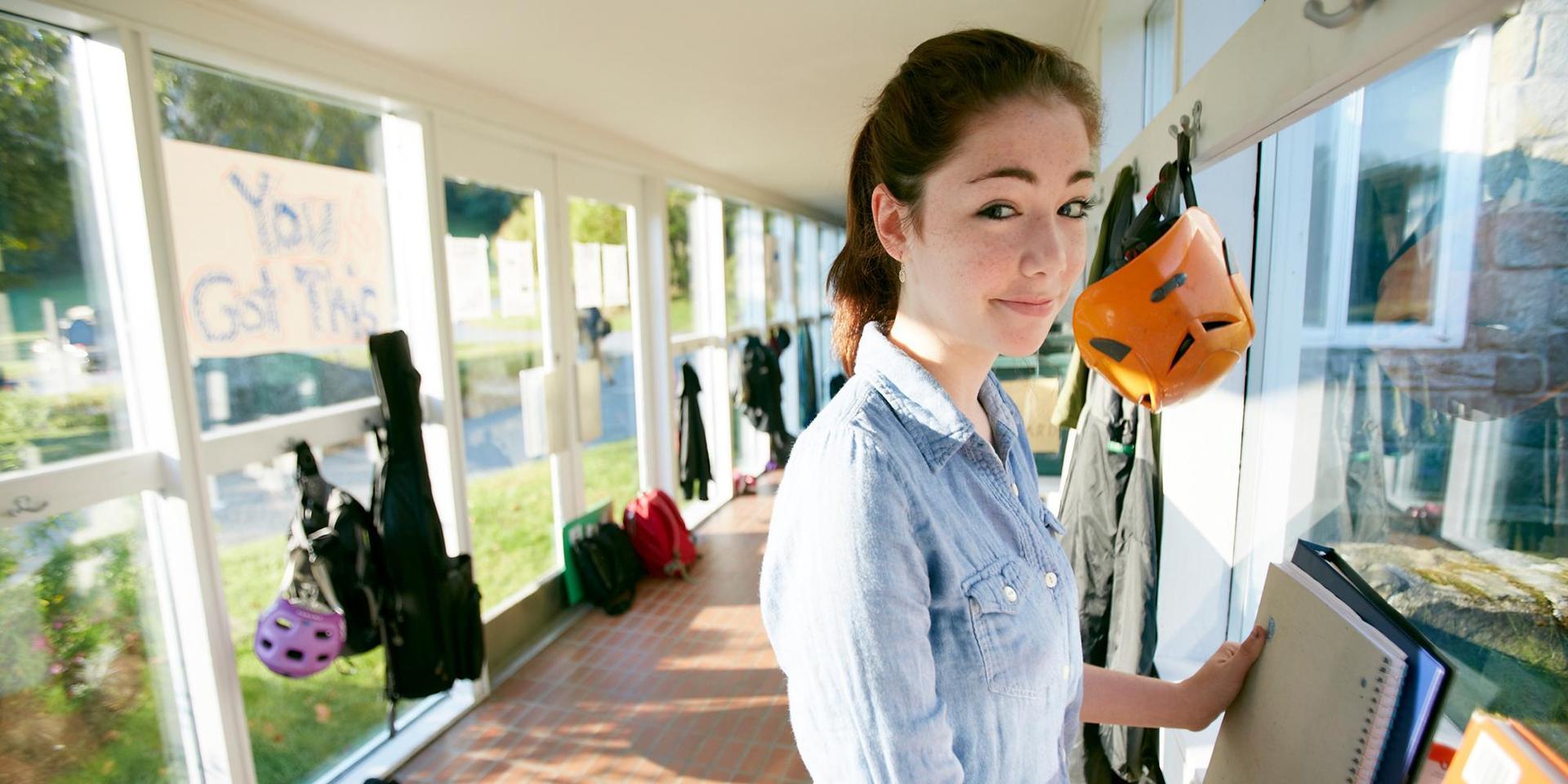 一个学生在玻璃走廊里填她的背包.