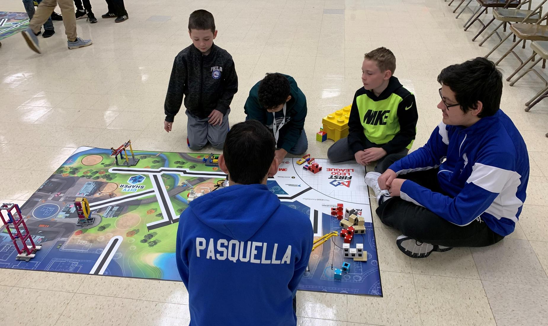 3 elementary students sitting with 2 high school students on a  FIRST LEGO League mat. They are coding robots.