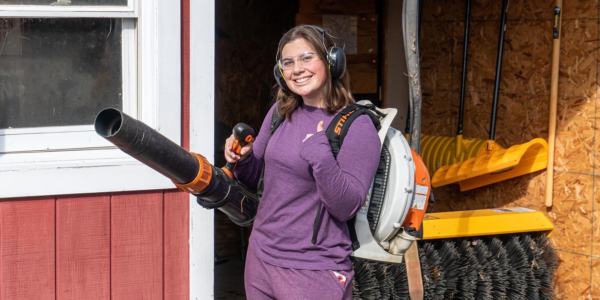 在社区服务日,一名学生带着吹叶机和安全设备准备开始工作.