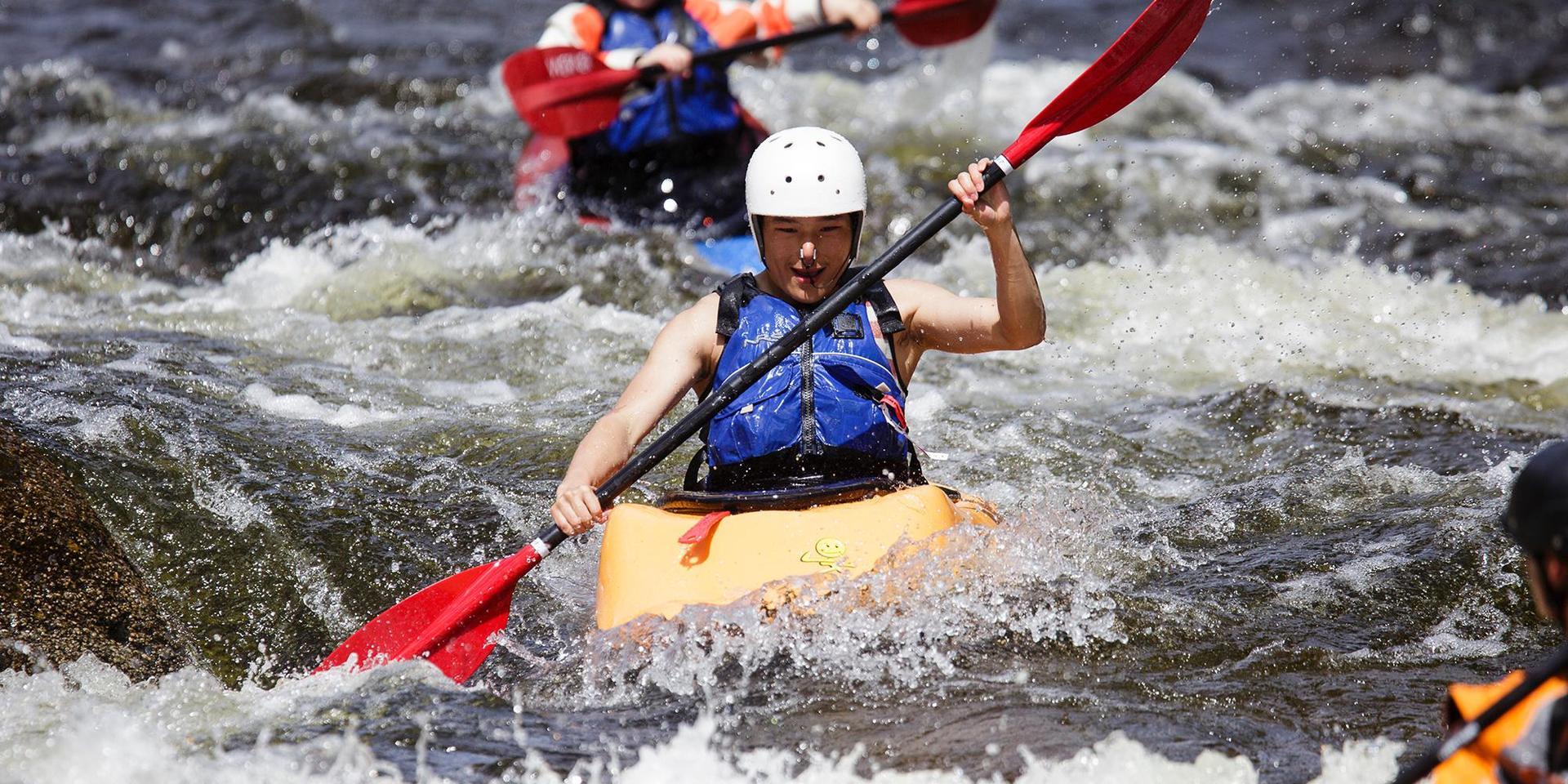 一个学生在激流中划皮艇.