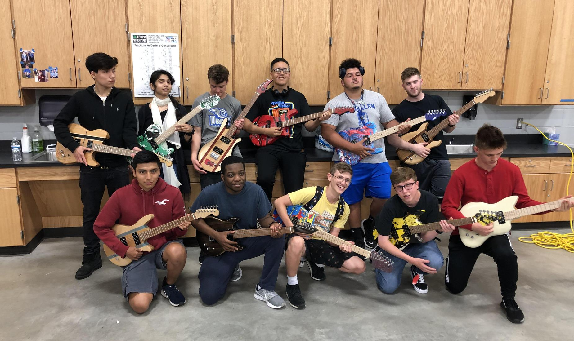 11 BHS STEM Students strumming wood guitars that they made in STEM Class
