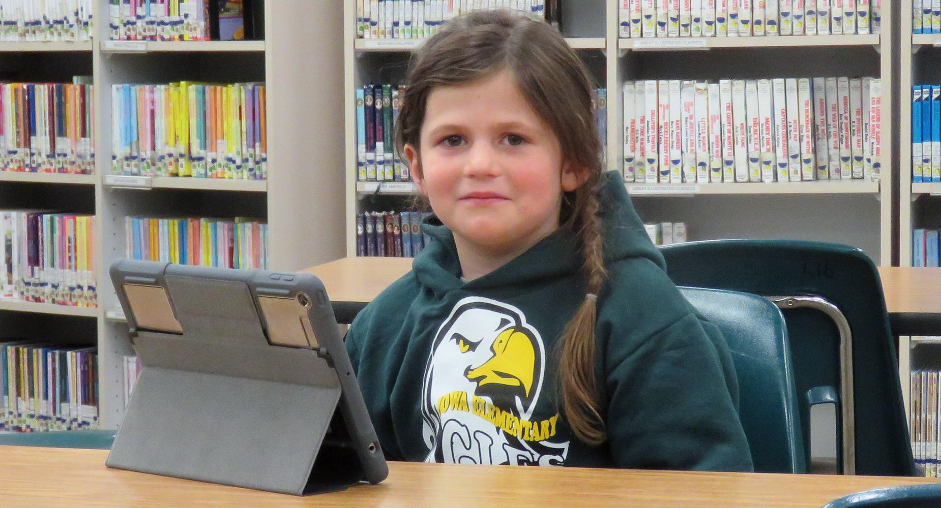 Iowa Elementary student (girl) with an iPad in the library.