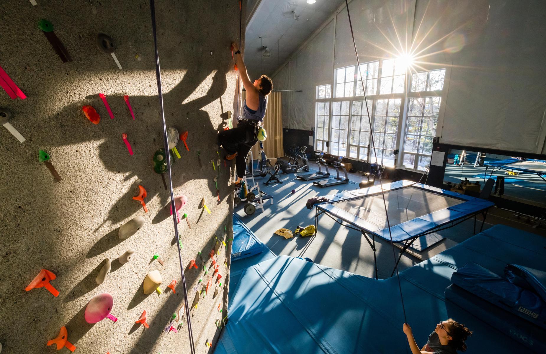 一个学生正爬到JDB电子攀岩墙的顶端.