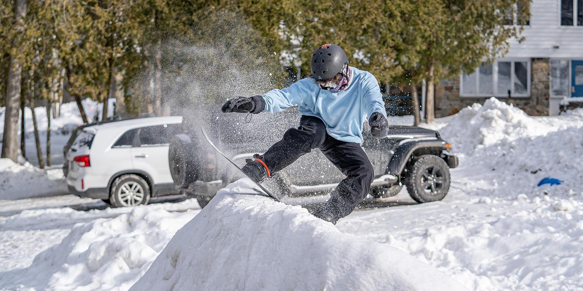 A student kicking up a cloud of snow after landing an impressive snowboard trick.