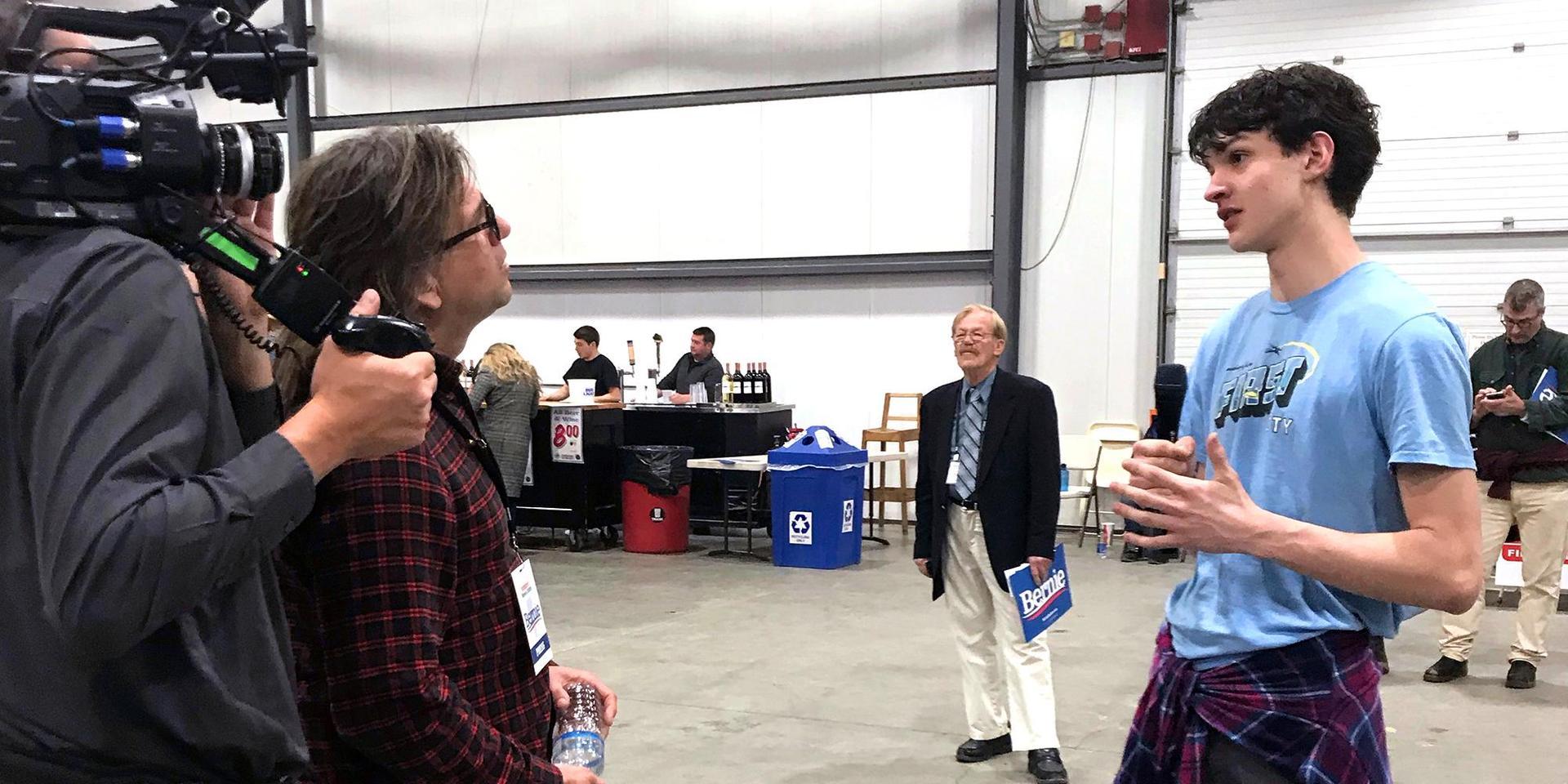 在政治集会上接受采访的学生.