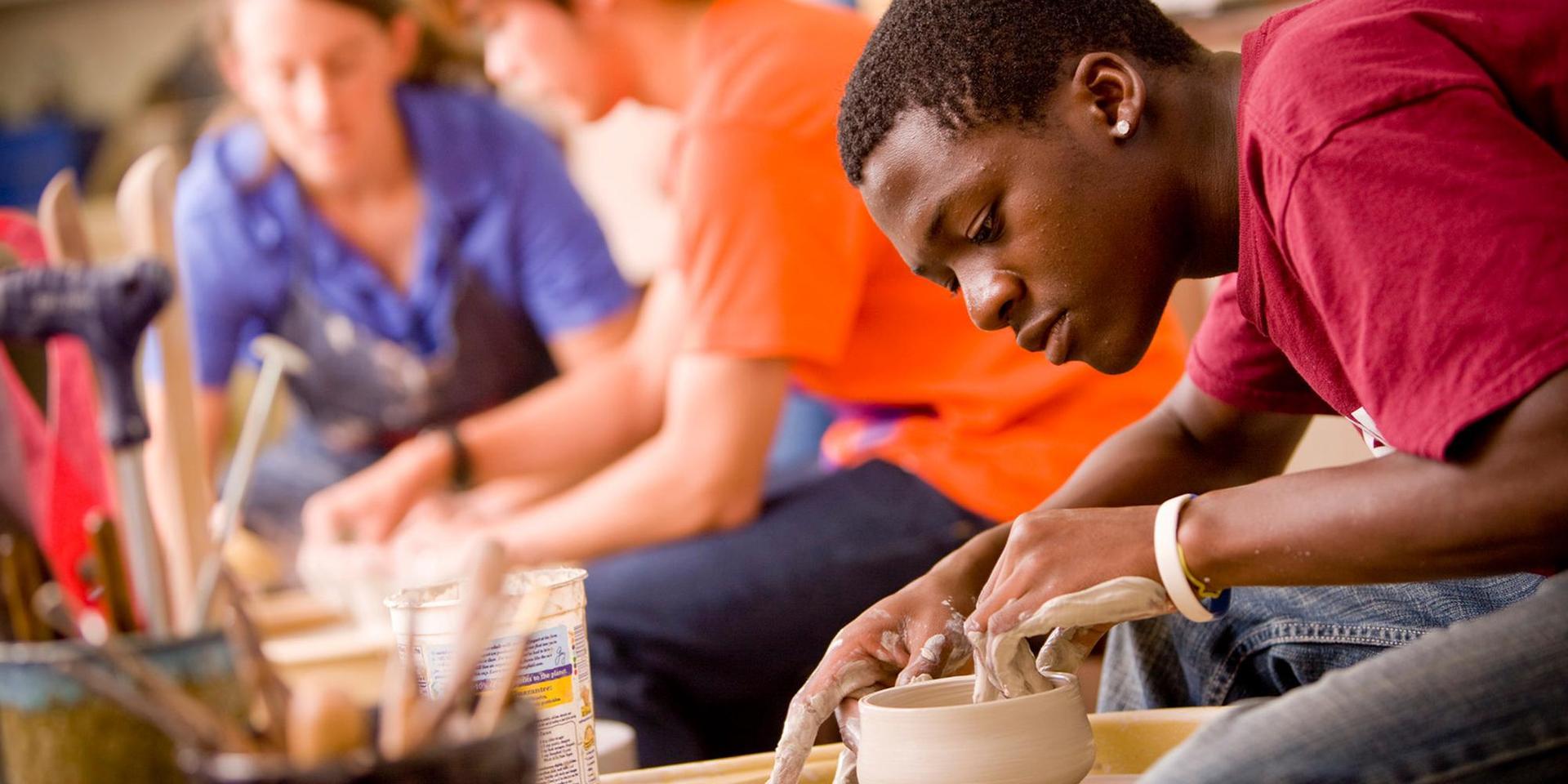 一个学生在陶瓷轮上投掷并塑造一个碗.