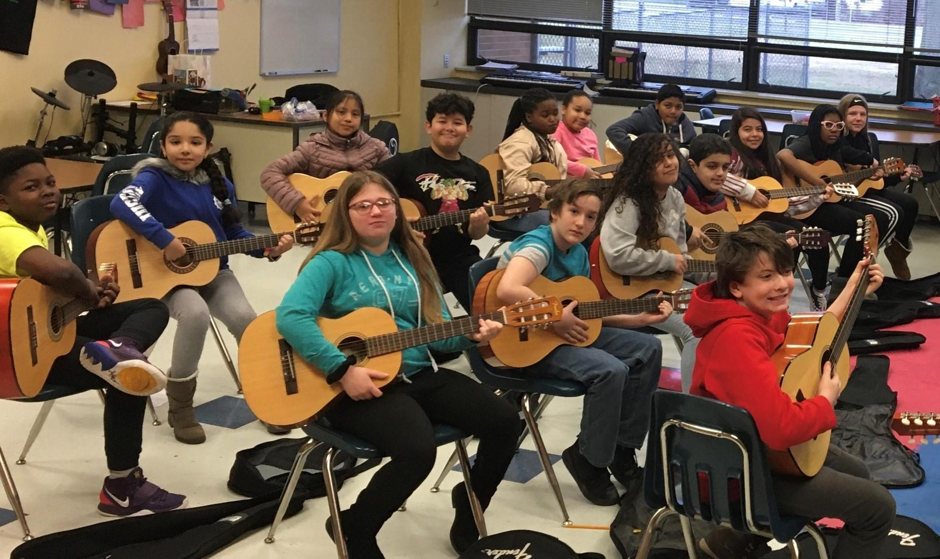 15 elementary school students in music classroom, each holding a guitar, smiling!