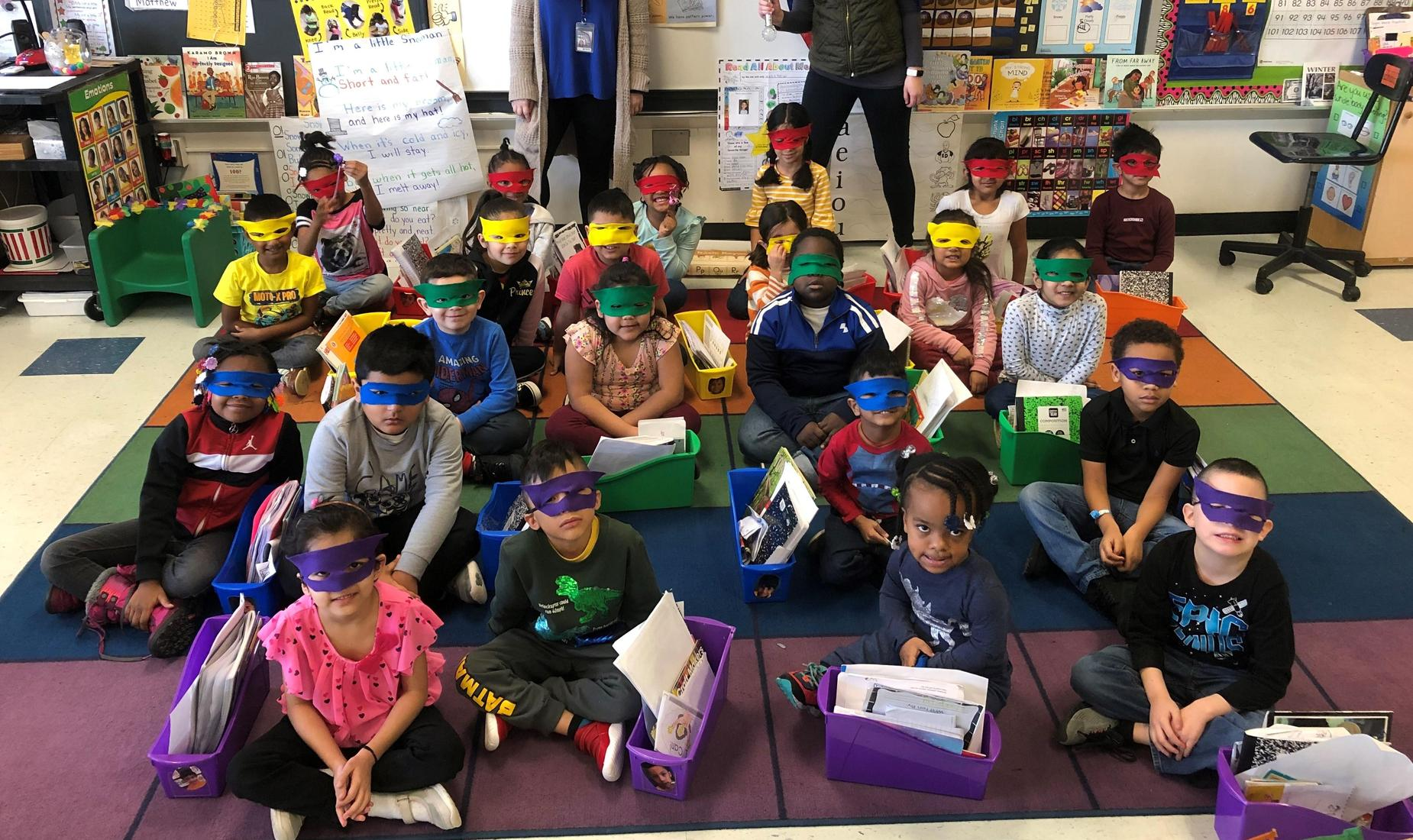 Girls and boys sitting on a colorful carpet wearing blue, purple, red, yellow eye masks. They are Super Readers.