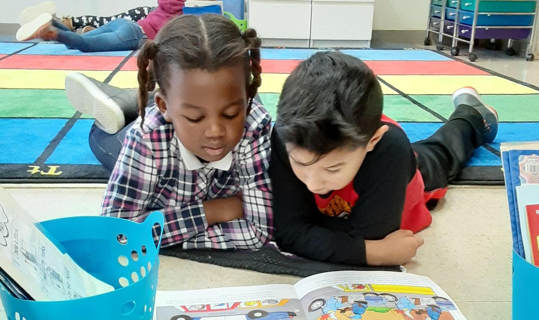 Little girl and little boy laying on their stomachs and leaning on their elbows, reading a Dr. Seuss book together