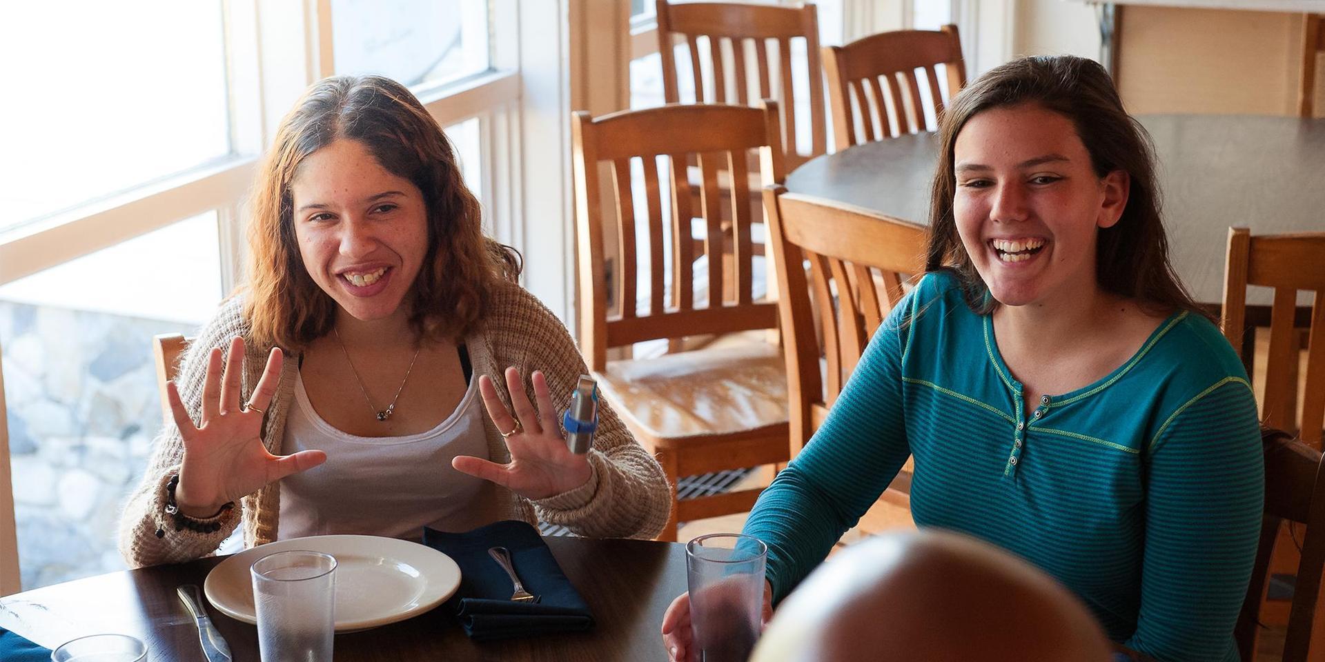 两名学生在餐厅的一张桌子上吃家庭式早餐.