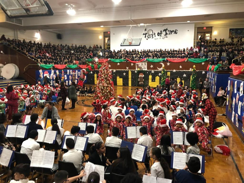 long photo of the school band, the children in their pjs with santa hats, older children in the bleachers with their parents watching the show