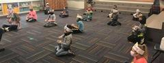 South School Elementary Students socially distanced and masked, sitting on the floor with percussion instruments in music class
