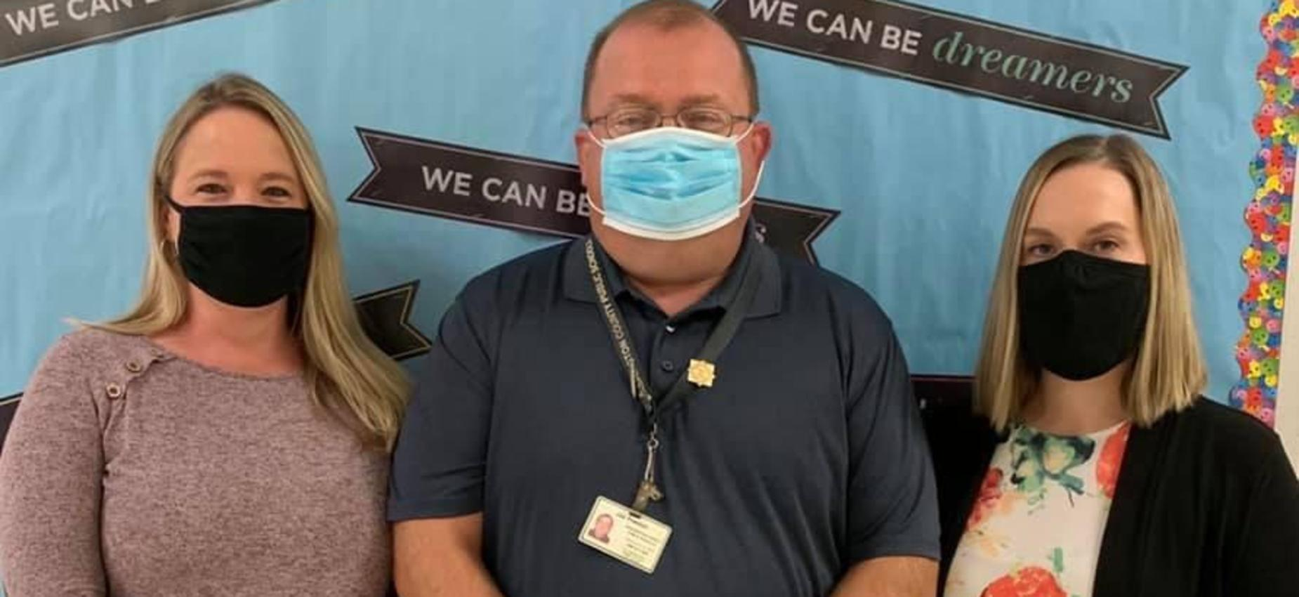 Three teachers wear masks in front of a bulletin board.
