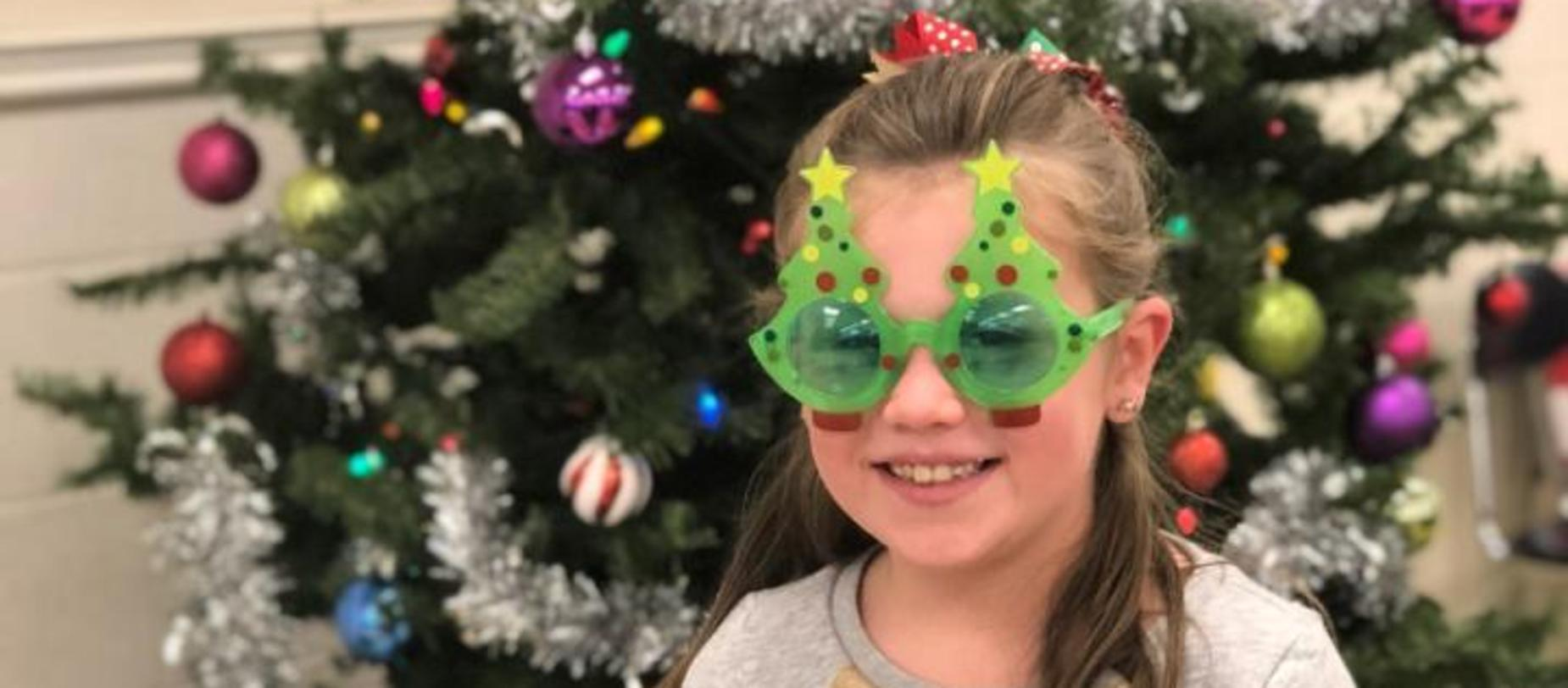 student wearing Christmas tree glasses