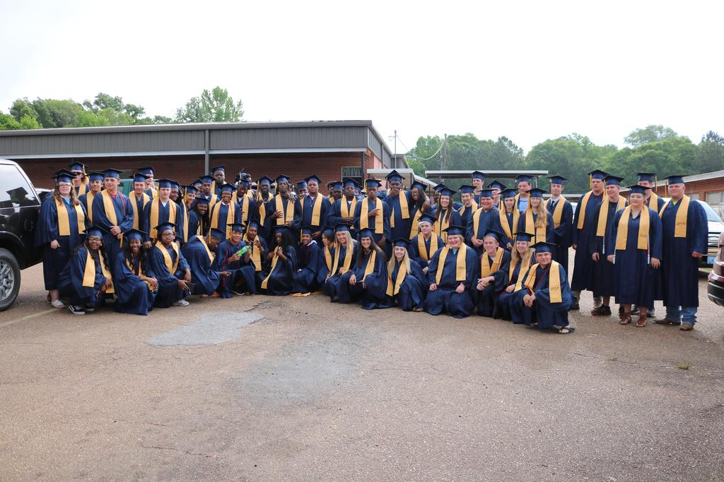 2017 seniors in parking lot wearing cap and gown