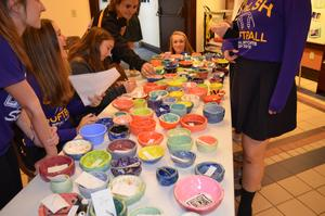Photo of students behind a table of colorful ceramic bowls