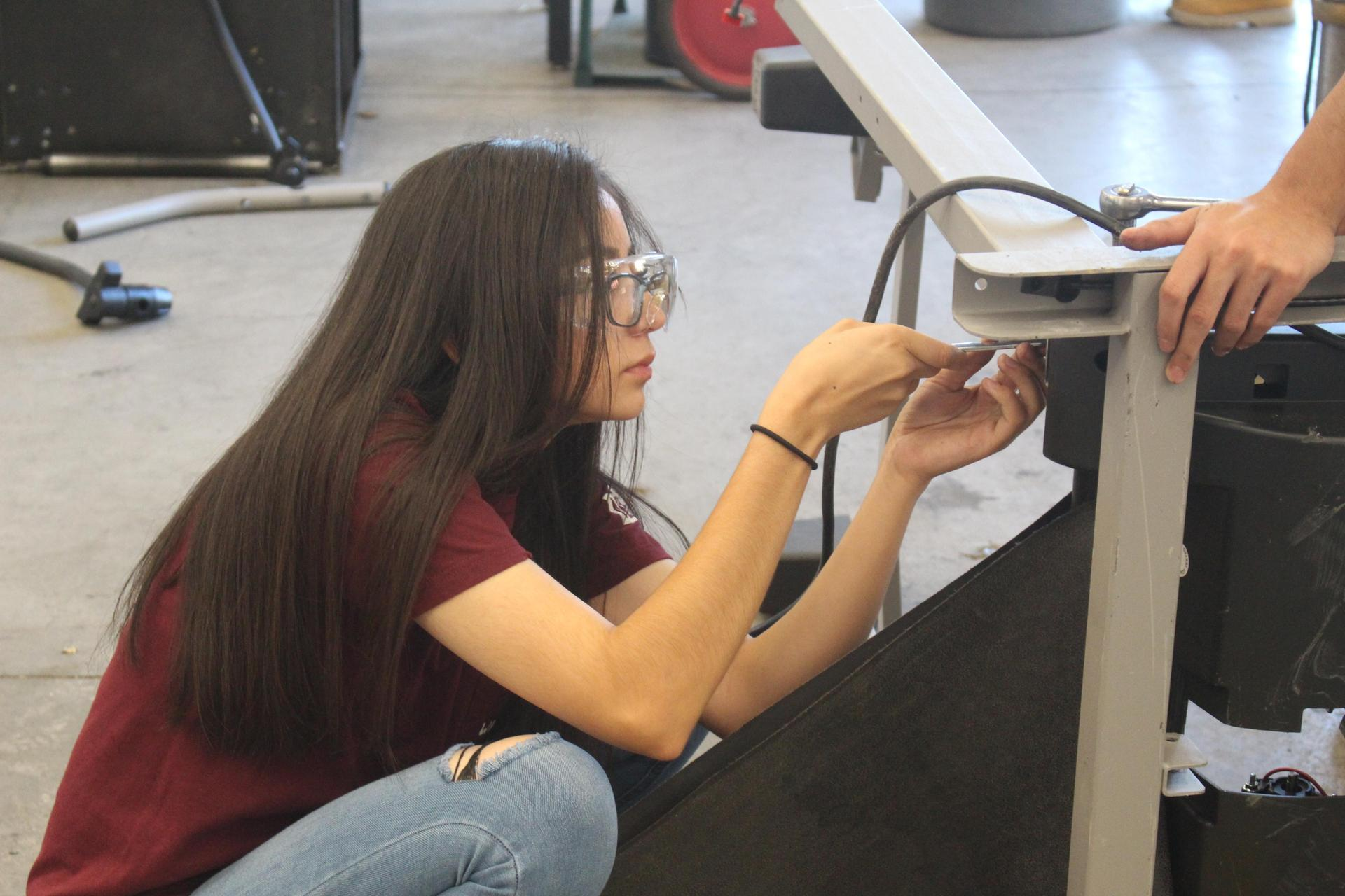 Female student helping put together a hoist
