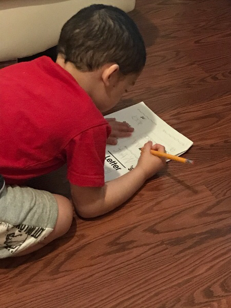 boy on the floor doing his work from home