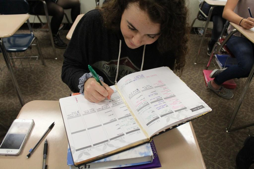 Student writing in a planner