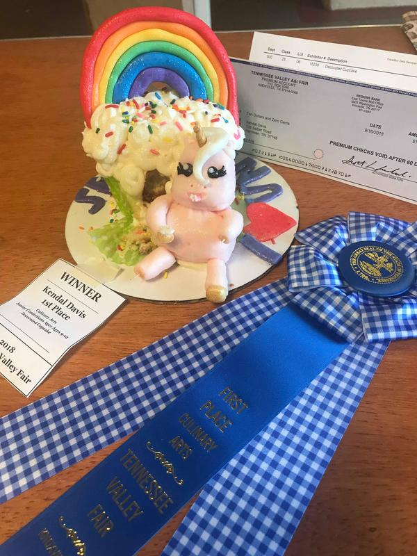 Fat unicorn eating a giant cupcake with the 1st place blue ribbon laying beside it