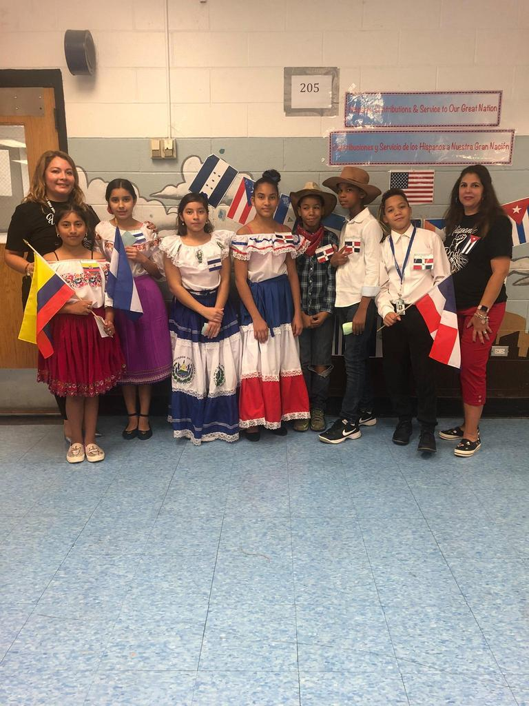 Mrs. Ramirez and Mrs. Camacho with several students wearing their folk attire
