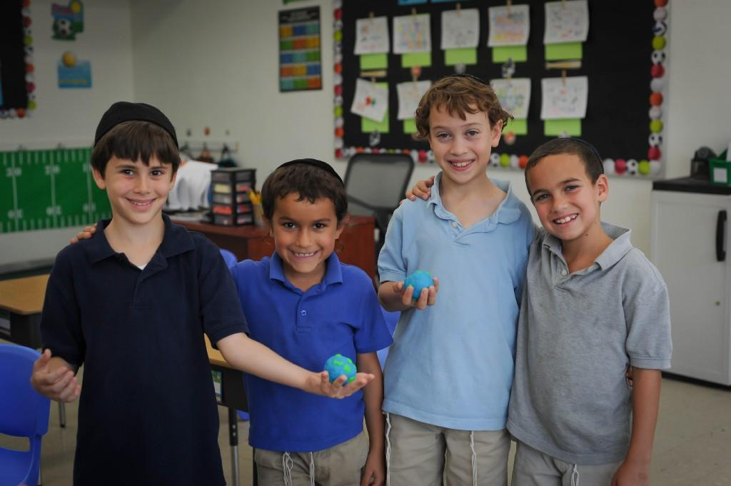 Boys holding their clay models of Earth