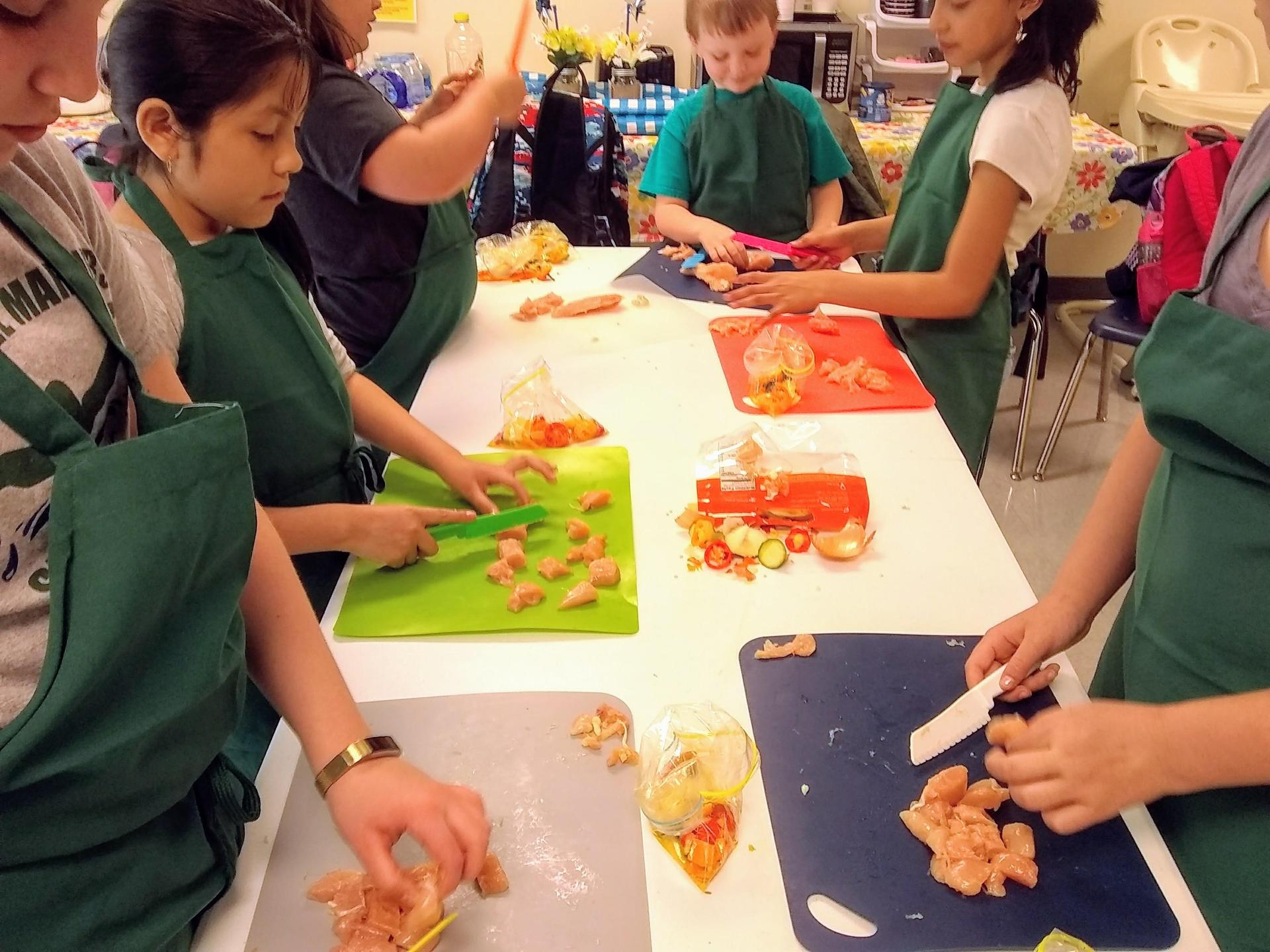 kids preparing chicken and vegetables for cooking