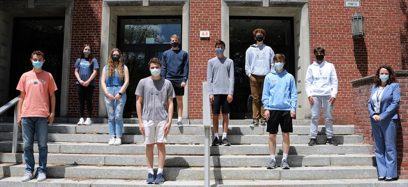 Photo of WHS students standing outside on steps with principal.