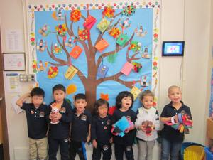 pre-k kids standing in front of their giving tree with their homemade turkeys