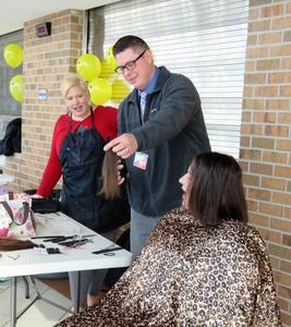 TKHS principal Tony Petersen snipped the pony tails off for the two teachers who donated hair.