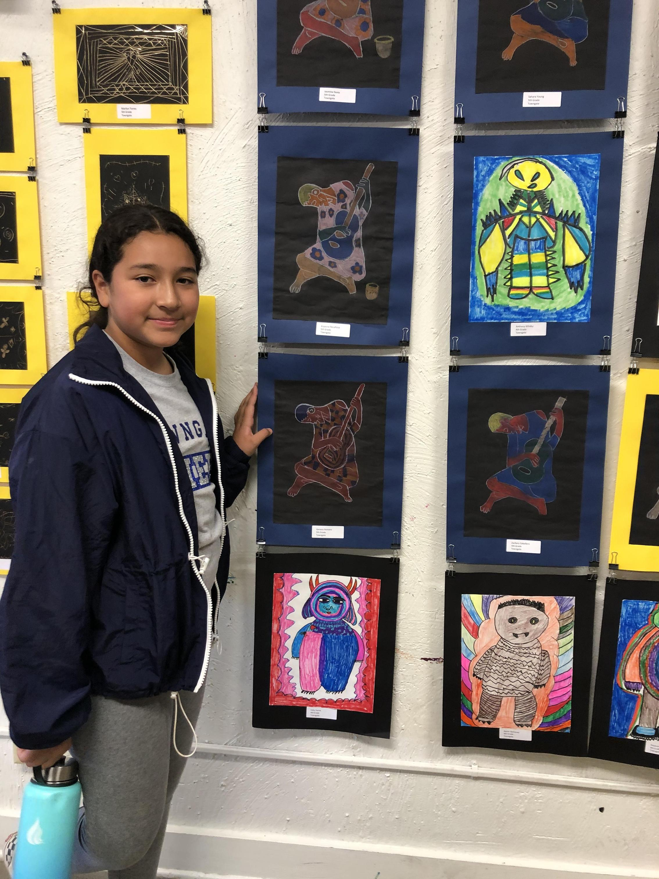Student posing next to their art