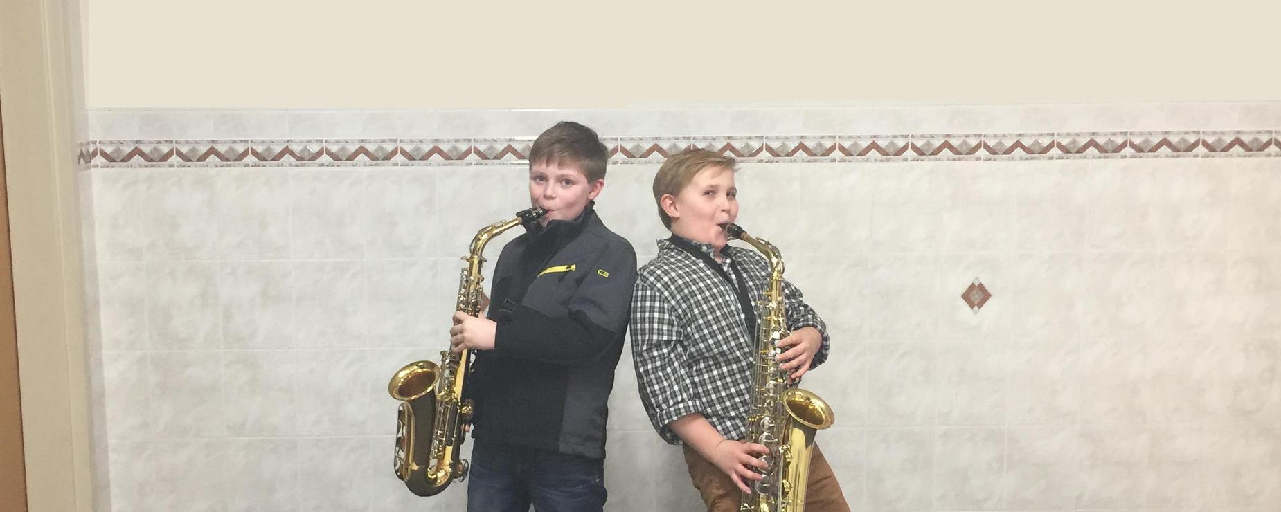 Two middle school boys stand back to back making funny faces while playing their saxophones