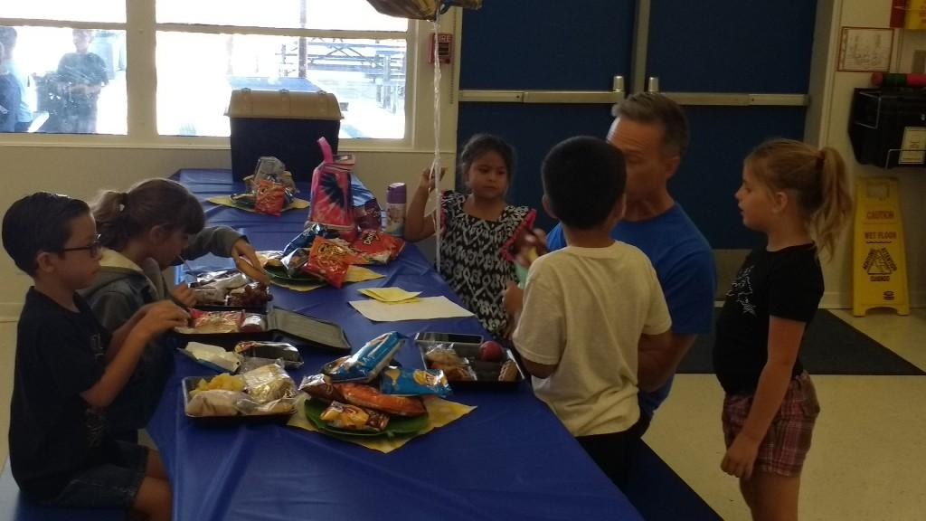 Mr. Broecker having lunch with first grader winners of Lunch with the Principal for August