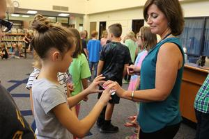 A teacher and a student each hold the energy baton to create electricity.