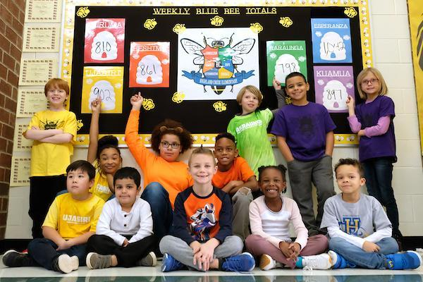 Students in front of a weekly blue bee totals board