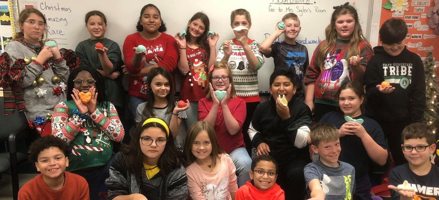 students pose with play dough creations