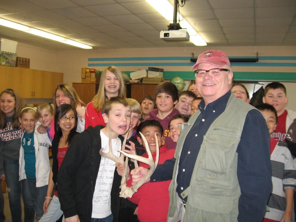 teacher with antlers in his hands poses for camera with students