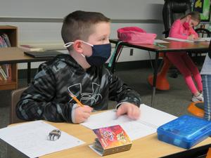 A student works on writing a letter to his pen pal.