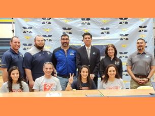 Geo sitting with her family, coaches standing behind her