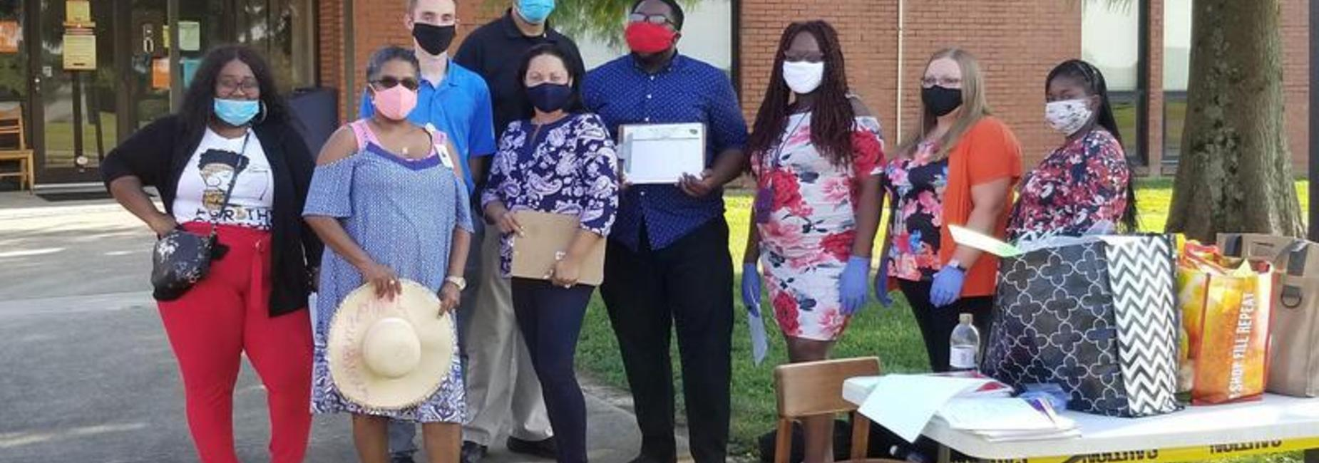 This is a picture of five of the Third Grade staff, the Guidance counselor, the Music teacher, and the Art teacher demonstrating the proper use of covid masks during the first DSJ Open House
