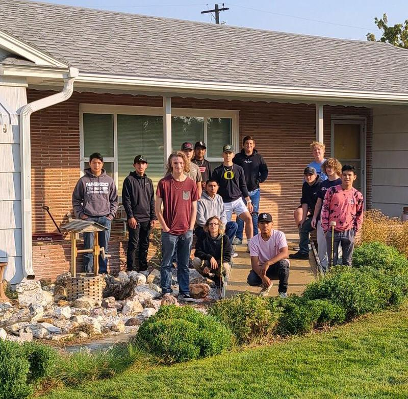 Construction students pose in front of the home where they built a ramp.