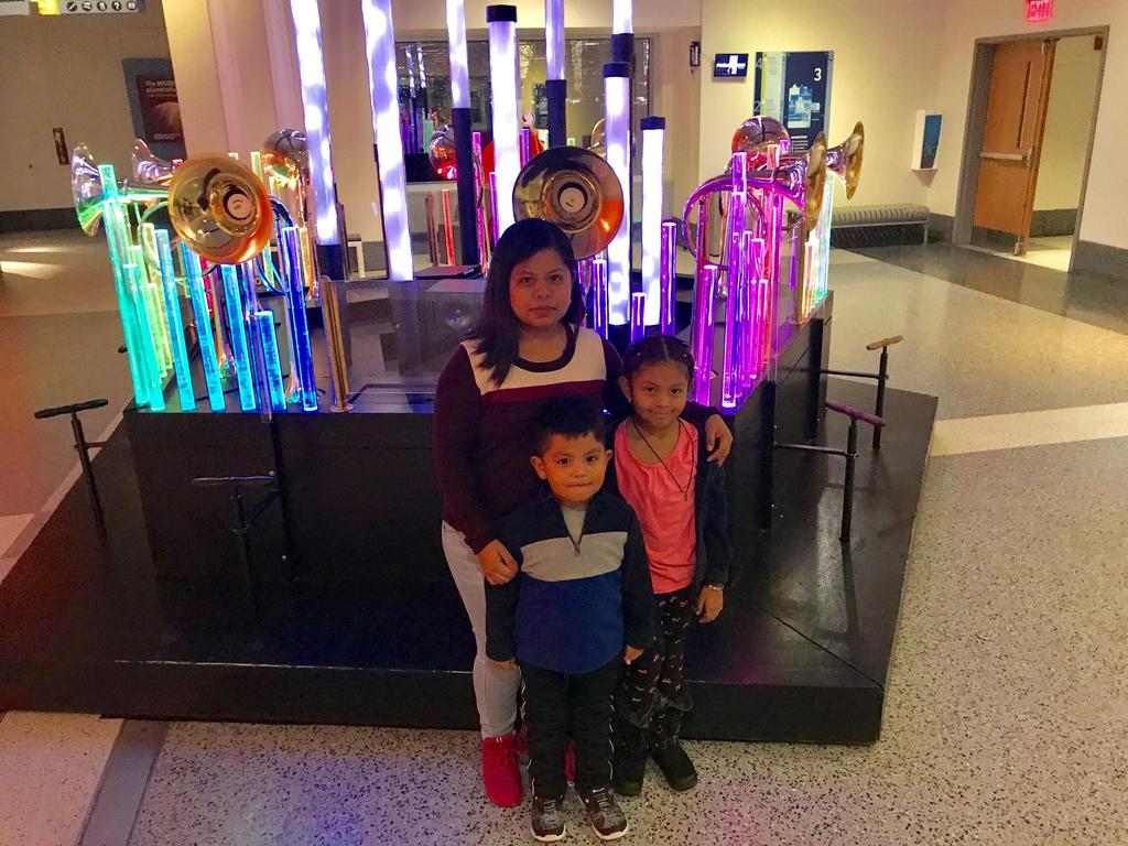 Happy mom with her daughter and son at the Liberty science center night